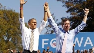 Barack Obama acknowledges the crowd with Virginia Senator Mark Warner during a campaign rally in Richmond, Virginia