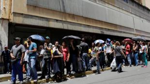 Venezolanos hacen una cola para comprar comida frente a un supermercado de Caracas, el 28 de abril de 2016.