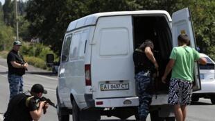 Des combattants rebelles inspectent des véhicules sur une route à proximité de Chakhtarsk, dans la région de Donetsk, le 28 juillet 2014.