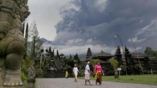 Des habitants de Karangasem devant le volcan Agung, crachant de la fumée, le 26 novembre 2017.
