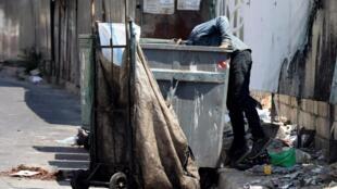 Un homme en train de fouiller dans une poubelle dans les rues de Beyrouth. (Illustration)
