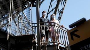 Des touristes portant des masques protecteurs visitent la tour Eiffel à Paris le jour de sa réouverture au public, le 25 juin 2020, à Paris.