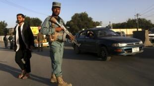 Un policier afghan monte la garde à un point de contrôle dans Kaboul, le 17 août 2015, alors qu'une humanitaire allemande a été sortie de force de sa voiture et enlevée par un homme armé.