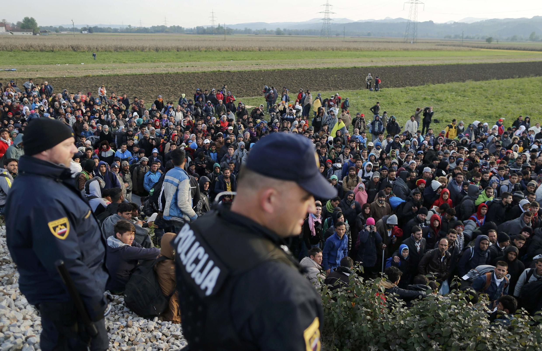 Policiais eslovenos observam filas de migrantes