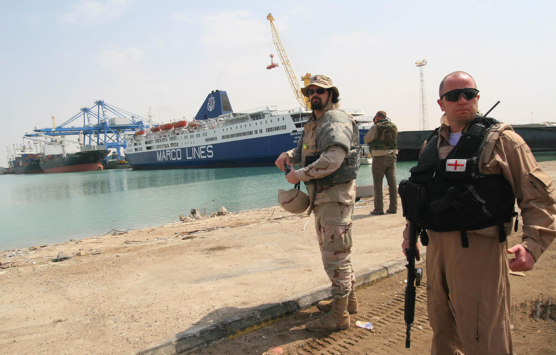 """Un membre de la SMP britannique Aegis protège des """"contractors"""" américains supervisant la livraison de véhicules pour les forces irakiennes à Umm Qasr, en 2008."""