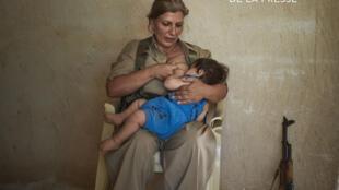 Souleimaniye, Irak, septembre 2014: Shaista, la peshmerga allaite son enfant de 10 mois.