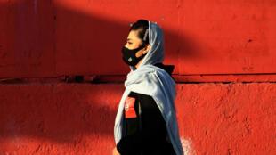 An Iranian woman wears a face mask as a Covid-19 coronavirus pandemic precaution in Iran's capital Tehran