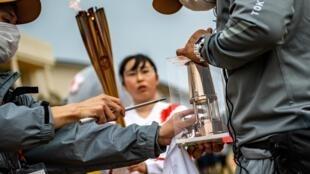 Un membre de l'organisation de Tokyo 2020 transfère la flamme olympique à son relais basé à Tomioka Daiichi, le 25 mars 2021