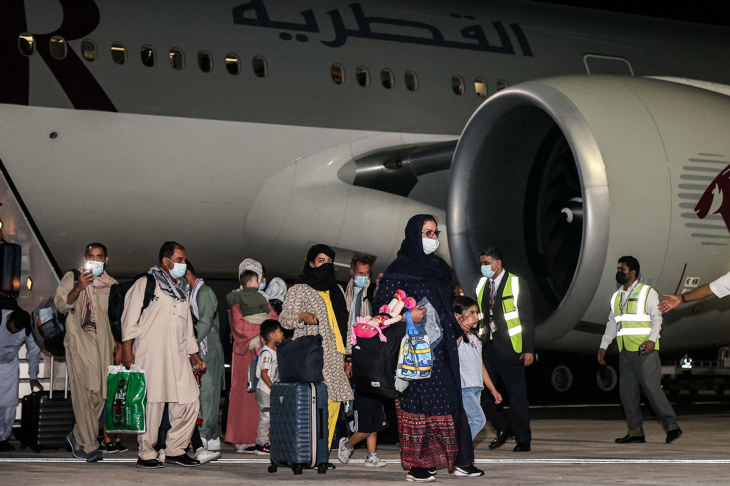 Evacuees from Afghanistan arrive at Hamad International Airport in Qatar's capital Doha on the first flight carrying foreigners out of the Afghan capital since the conclusion of the US withdrawal last month