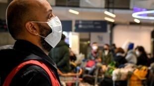 Nhân viên sân bay mặc bảo hộ, mang khẩu trang, tại sân bay Roissy-Charles De Gaulle, Pháp, giám sát hành khách từ Trung Quốc tới, ngày 26/01/2020