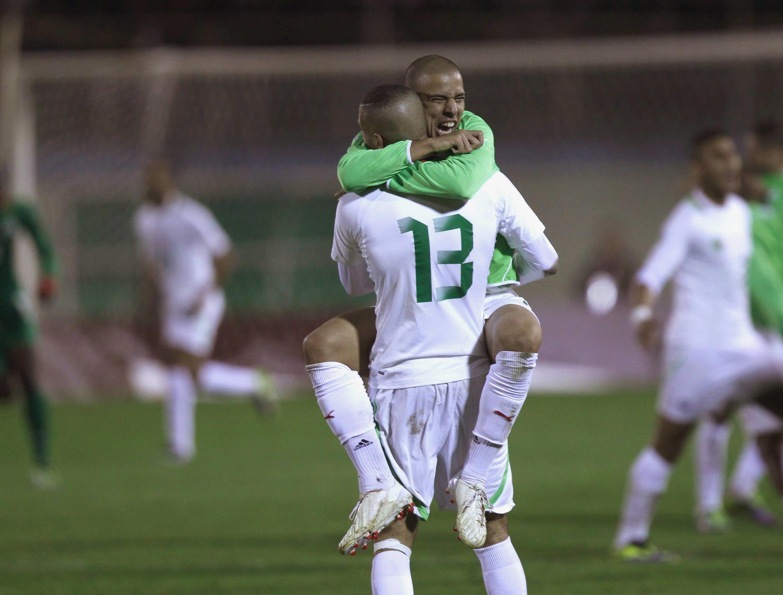 L'Algérien Sofiane Feghouli dans les bras d'Islam Slimani après la qualification de l'Algérie pour la Coupe du monde 2014.