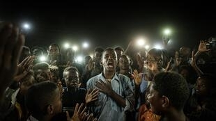 Yasuyoshi Chiba won the 2020 World Press Photo award for his photo of a young Sudanese man reciting a poem while protesters light him up with cell phones, Khartoum, 19 June 2019.