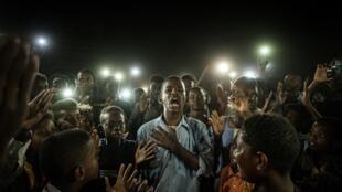 En esta foto de archivo un joven sudanés recita un poema en medio de manifestantes que lo iluminan con celulares, el 19 de junio de 2019 en Jartum. Su autor el fotógrafo de la AFP Yasuyoshi Chiba ganó el premio World Press Photo del año 2020