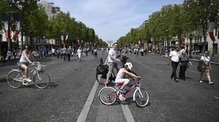 People ride bicycles and walk on the Champs-Elysees Avenue in Paris, on May 8, 2016, as French capital's most famous avenue goes car-free for a day