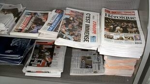 French and international newspapers are lined up on two racks
