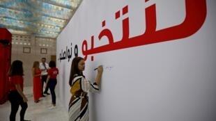 Des Tunisiens écrivent et signent un grand panneau sur lequel est inscrit : «Nous élisons et nous continuons», lors de l'ouverture de la salle de presse pour l'élection présidentielle, le 12 septembre à Tunis.