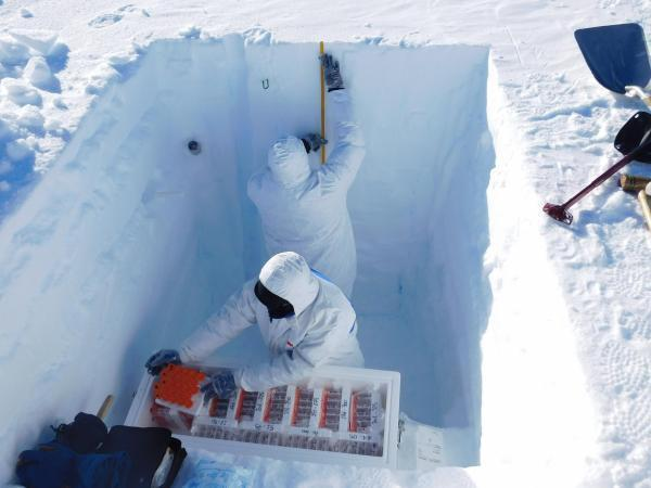 Taking snow samples from a well. The mission collected several hundred samples of snow that will help scientists measure how the climate behaved in past eras.