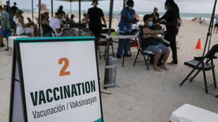 People get a Johnson & Johnson Covid-19 vaccine at a pop-up vaccination center at the beach, in South Beach, Florida, on May 9, 2021