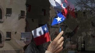 Une personne agée agite un drapeau chilien pendant les «fêtes de la patrie» à Santiago le 16 septembre 2020.