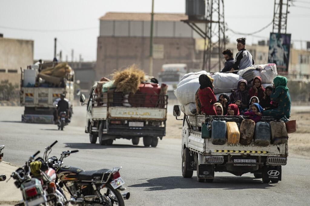 Des Syriens déplacés à l'arrière d'une camionnette pendant que des civils arabes et kurdes s'enfuient face à l'attaque militaire turque, le 11 octobre 2019, dans la ville frontalière syrienne de Tal Abyad.