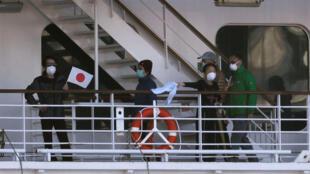 Hành khách trên tàu Diamond Princess neo tại Yokohama, Nhật Bản vẫy chào báo chí, ngày 12/02/2020.