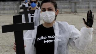 Des activistes brandissent des croix faisant référence aux 400.000 décès liés au Covid-19 au Brésil lors d'une manifestation contre la gestion par le gouvernement de la pandémie devant le palais présidentiel de Planalto à Brasilia, le 1er mai 2021.