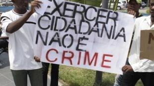 Jovens angolanos, exibindo cartaz durante manifestação, defendendo a cidadania, em solidariedade com os 15+1 jovens activistas presos por tentativa de golpe de estado em Angola