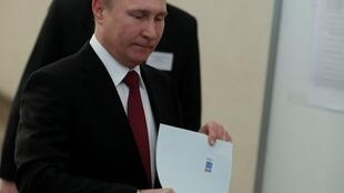 Russian President and Presidential candidate Vladimir Putin casts his ballot in Moscow