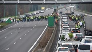 Protesters wearing yellow vests (gilets jaunes) block the ring road near La Roseraie district of Toulouse, on December 15, 2018 as they demonstrate against rising costs of living they blame on high taxes.