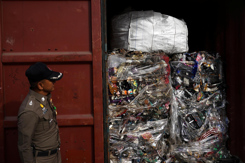 Un policía observa los desechos electrónicos que se encuentran en un contenedor durante un allanamiento en el puerto de Leam Chabang, en Tailandia.