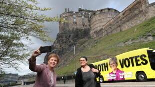 La Première ministre écossaise et chef du Parti national écossais (SNP) Nicola Sturgeon prend un selfie avec une femme avec le château d'Édimbourg en arrière-plan, alors qu'elle fait campagne, le 1er mai 2021.