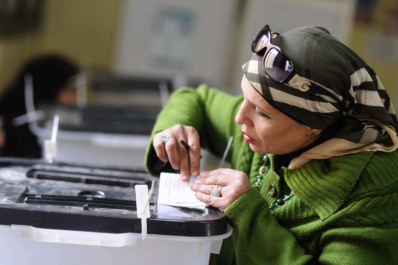 Une électrice glisse son bulletin dans l'urne, dans un bureau de vote du Caire.