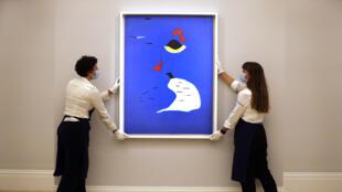 Les employés de Sotheby ajustent un tableau de Joan Miro intitulé «Peinture (Femme au chapeau rouge)» dans la salle de ventes Sotheby's à Londres. Ce tableau a été vendu 22,3 millions de livres (28,9 millions de dollars) lors d'une vente aux enchères virtuelle de Sotheby's, le 28 juillet 2020.