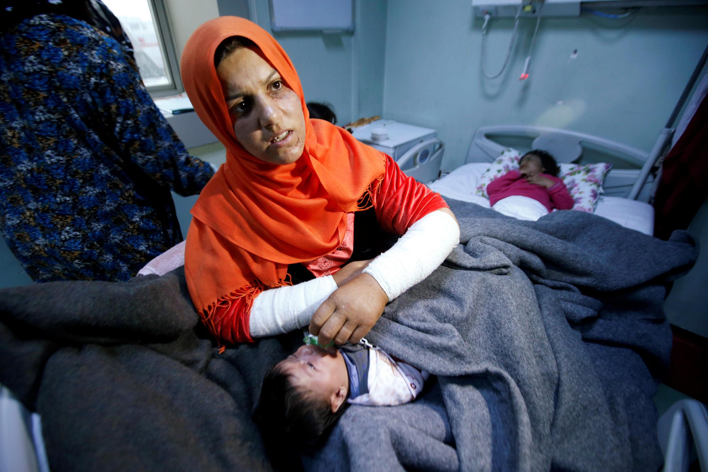 Une mère de famille attend que des soins soient prodigués à son enfant, à l'hôpital ouest d'Erbil, le 4 mars 2017.