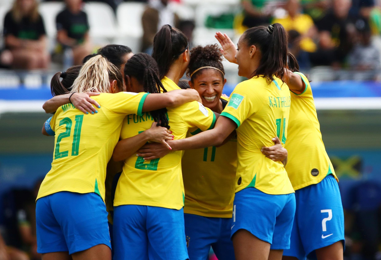Cristiane, de frente, é abraçada pelas companheiras de equipe ao celebrar um de seus três gols contra a Jamaica na estreia do Brasil na Copa do Mundo.