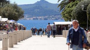 Les gens marchent près de la mer le 21 avril 2016 à Zadar, en Croatie.
