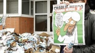 Сотрудник редакции карикатурист Люц (Luz)держит сгоревший номер газеты Charlie Hebdo «Charia Hebdo»