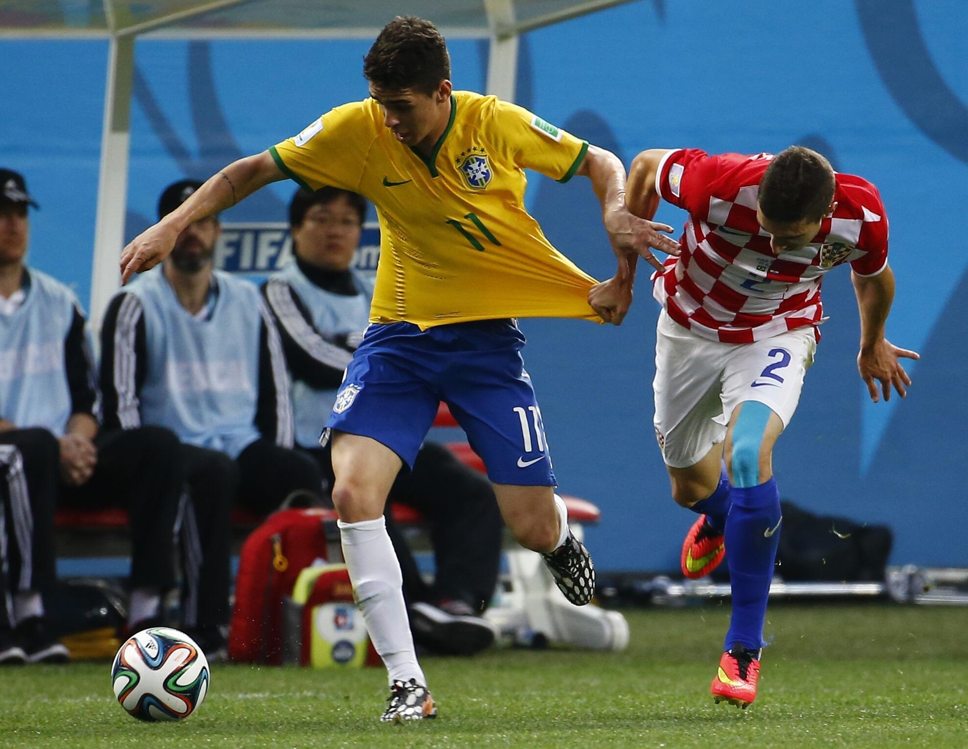 Entre Hernanes du Brésil (à gauche) et Vrsaljko de la Croatie (à droite), duel acharné lors du match d'ouverture du Mondial.