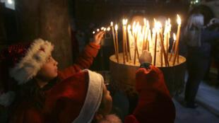 Des enfants allument des cierges pour Noël dans l'église de la nativité à Bethléem
