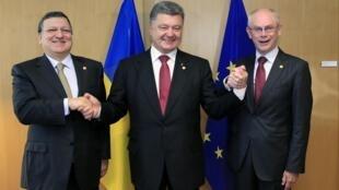 Petro Porochenko (centro) aperta as mãos de líderes europeus, José Manuel Barroso (esq.) e Herman Van Rompuy.