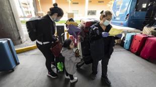 Pasajeros que acaban de aterrizar esperan ser trasladados a las instalaciones designadas para cumplir con una cuarentena de diez días impuesta a los viajeros en medio de la pandemia del nuevo coronavirus, en el Aeropuerto Internacional Arturo Merino Benítez, en Santiago, el 1 de abril de 2021