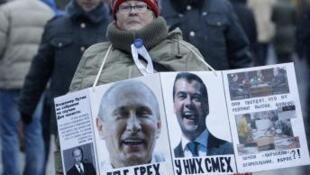 """Una Moscovita expresa su descontento contra Vladimir Putin y Dmitri Medvedev. """"Cuando hay una falta , se ríen"""" lee la pancarta."""