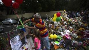 Homenagens diante da casa de Mandela em Johannesburgo, neste domingo.