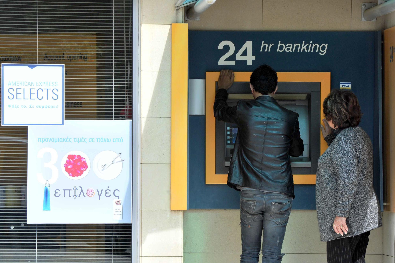 Des Chypriotes retirent de l'argent à une caisse automatique, le 16 mars 2013. Des files d'attentes se sont créées devant les automates après l'annonce d'un plan d'aide européen controversé.