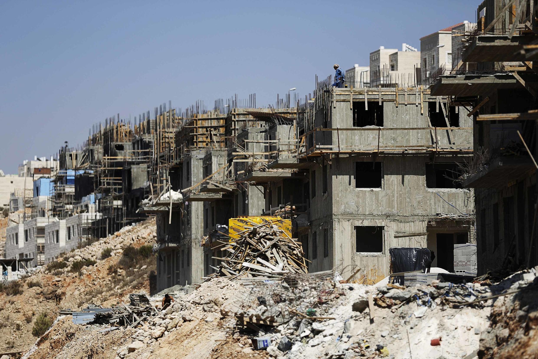 Des ouvriers palestiniens travaillent sur un chantier de constructions de nouvelles colonies en Cisjordanie, le 11 août 2013.