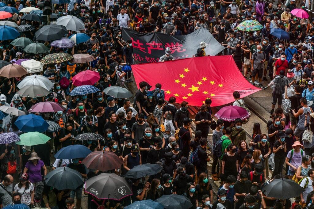 Des manifestants pro-démocratie marchent dans Hong Kong, le 31 août, portant une bannière rouge où est dessiné un swastika nazi.