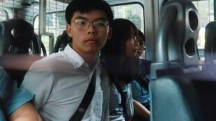 Os activistas pró-democracia Joshua Wong e Agnes Chow chegam ao Tribunal após terem sido detidos por suspeita de terem organizado protestos ilegais, em Hong Kong.