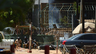 Security personnel take cover as smoke billows from The Institute Francais in Ouagadougou on March 2, 2018, as the capital of Burkina Faso came under multiple attacks targeting the French embassy, the French cultural centre and the country's military HQ.