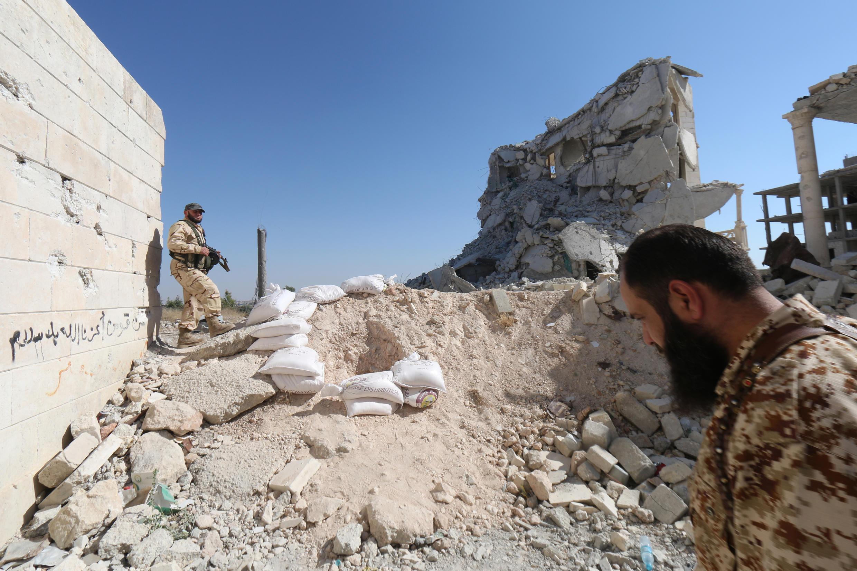 Des rebelles syriens dans les ruines du centre de recherche à Alep, une position de l'armée régulière dont ils se sont emparés samedi 4 juillet.