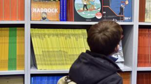 Un jeune garçon parcourt du regard toute une collection de bandes dessinées lors du 43e festival international de la BD d'Angoulême.